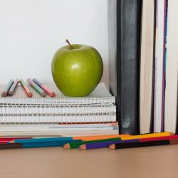 Back to school supplies. Books, pencils, notebooks and green apple