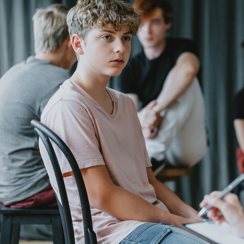School psychologist analyzing the teenager's behavior during workshops